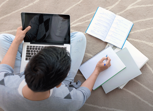 Student holding laptop with study notes